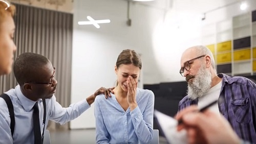 A group of people sit in a white room. A woman appears to be crying in the center of the image, she is comforted by a man with glasses on the left, and a man with a large white beard on the right.