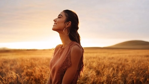 A woman with long brown hair and large hoop earrings stands in a golden field, looking contentedly off into the sunset.