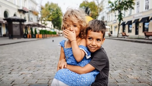 A young girl child wearing a blue eyelet dress sits on the lap of a young boy child wearing a dark grey t-shirt.