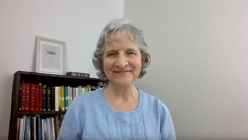 Karin sits smiling at a desk in front of a white wall and a bookcase full of Swedenborg's writings.