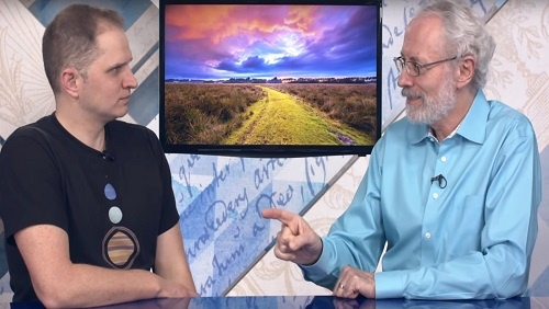 Curtis and Jonathan sit at the anchor desk, an image of a path through a field on a screen between them.