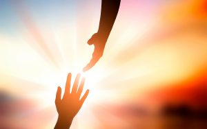 A photograph of two hands reaching toward each other in front of a bright luminous light.
