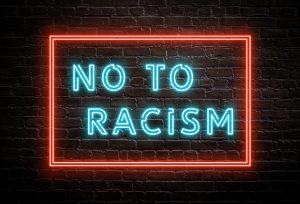 NO to Racism - neon message on brick wall