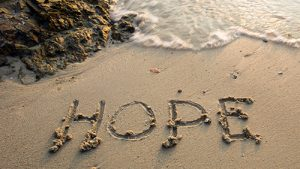 "A photograph of the word ""Hope"" written in the sand at a beach."