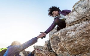 A photograph of two people working together to climb a large rock. A woman at the top of the rock reaches her hand down to assist another person in climbing up.