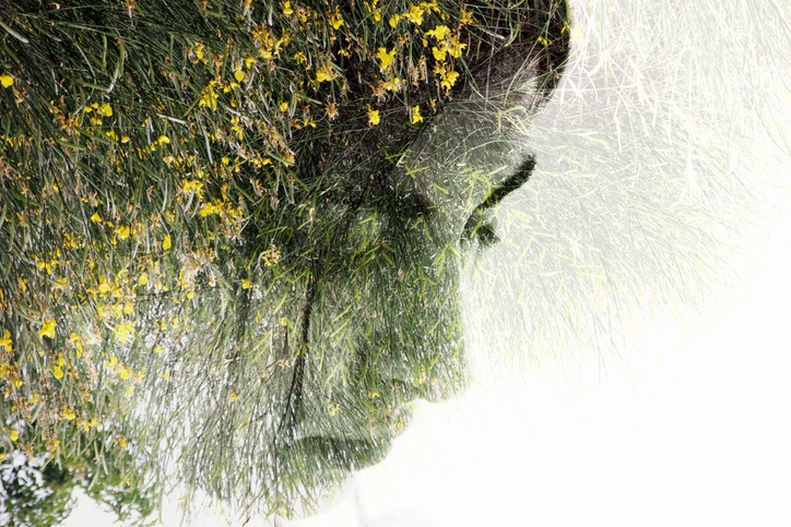 An image of a woman's face, with an overlay of green leaves and flowers.