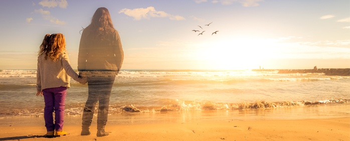A child stands on a sunset beach, holding hands with a person with long hair, who is slightly transparent, as if they aren't in the physical world.
